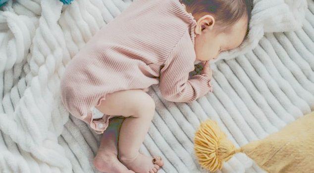 Sommermode für Babys. Baby auf Decke