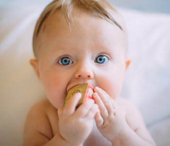 Wenn Babys zahnen: Baby steckt Holzklotz in Mund