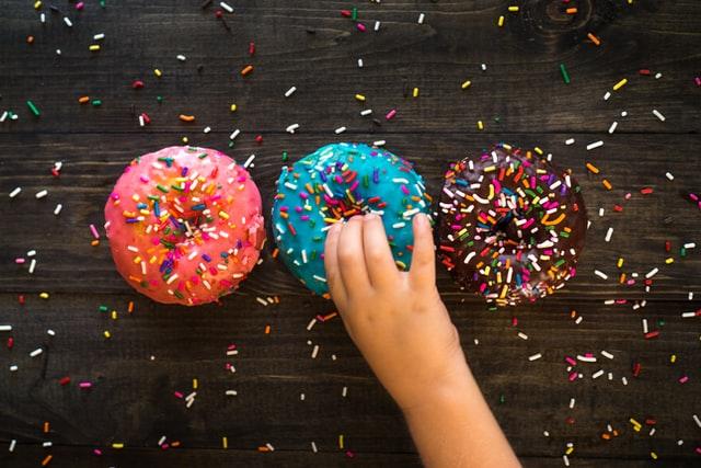 Essen für Kinder: Kind nimmt Donut