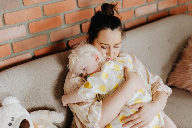 Kinderkrankheiten: Mutter hält Kleinkind im Arm